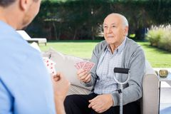 Male Caretaker And Senior Man Playing Cards Stock Photo