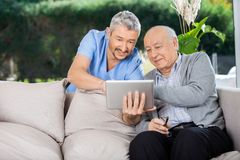 Male Caretaker And Senior Man Using Tablet PC. Male caretaker and senior men using tablet PC at nursing home porch royalty free stock image