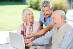 Male Caretaker Showing Something To Senior Couple Stock Photo