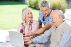 Male Caretaker Showing Something To Senior Couple. On laptop at nursing home stock photo
