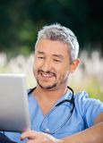 Male Caretaker Smiling While Looking At Tablet. Computer at nursing home porch royalty free stock images