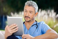 Male Caretaker Using Tablet PC While Sitting Stock Photo