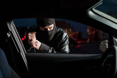 Male carjacker open car door with screwdriver. Male carjacker with balaclava on his head trying to open car door with screwdriver. Thief unlock vehicle. Auto Stock Photo