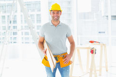 Male carpenter carrying planks in building Stock Photography