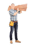 Male carpenter carrying planks over his shoulder Royalty Free Stock Photography