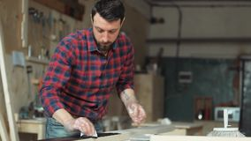 Male carpenter handles the wood in the carpentry workshop. Man wearing protective gloves handles wood protective liquid stain stock video footage