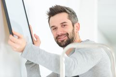 Male carpenter hanging picture frame on wall at home. Man stock image