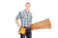 Male carpenter holding a couple of planks Royalty Free Stock Photography