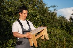 A male carpenter is holding a wooden stool royalty free stock images