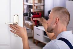 Carpenter Installing Door Lock. Male Carpenter Installing Door Lock With Wireless Screwdriver royalty free stock image