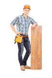 Male carpenter leaning on a plank. Full length portrait of  male carpenter leaning on a plank isolated on white background Royalty Free Stock Images