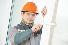 Male carpenter at lock installation. Male worker handyman carpenter at lock installation into wood door Stock Photos