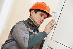 Male carpenter at lock installation. Male worker handyman carpenter at lock installation into wood door Stock Photo