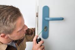 Male Carpenter Lubricating Door Royalty Free Stock Photo