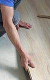 Male carpenter puts the laminate Stock Photography