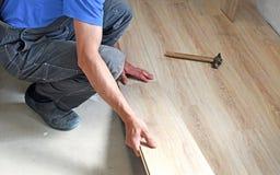 Male carpenter puts the laminate Stock Photos