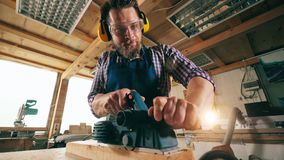 Male carpenter is sawing wood mechanically. Carpenter in carpentry workshop stock video footage