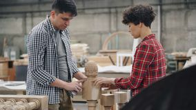 Male carpenter talking to female apprentice in workshop discussing woodware