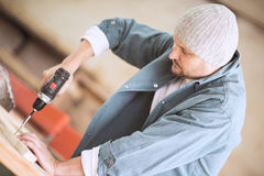 Male carpenter using drill in his workshop. Carpenter drilling hole in plank, in his workshop Royalty Free Stock Image