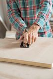 Male Carpenter Using Planer On Wooden Plank Royalty Free Stock Photos