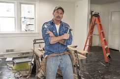 Male carpenter wearing leather tool belt and holding hammer lean. Ing against saw horse table with chop saw in home remodel during construction Royalty Free Stock Photography
