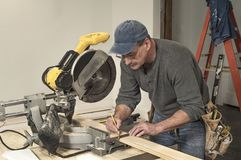 Male carpenter wearing tool belt and using square tool to mark wood board for cutting on professional chop saw. Male carpenter wearing tool belt and marking line stock images
