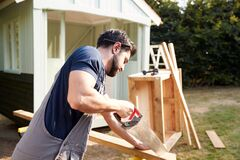 Free Male Carpenter With Female Apprentice Sawing Wood To Build Outdoor Summerhouse In Garden Royalty Free Stock Images - 175157189