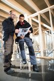 Male Carpenters Analyzing Plan At Construction Site Stock Photography