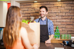 Male cashier being friendly to a customer Stock Photos