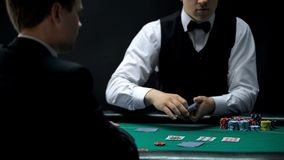 Male casino croupier dealing cards for businessman, chance to win at poker game. Stock photo royalty free stock image