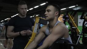 Male caucasian athlete is training his arms in the gym on the special equipment and his trainer is standing near. The sportsman is sitting on the special stock video footage