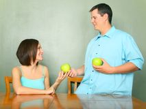 Male Caucasian Giving Green Apple To Young Woman Royalty Free Stock Photos