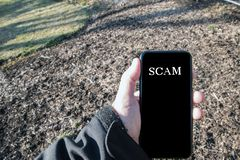 Male Caucasian hand in black jacket outdoors holding smartphone that says call is from spam. Male Caucasian hand in black jacket outdoors holding smartphone stock images