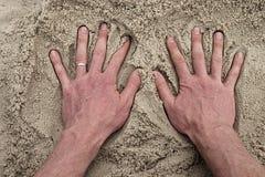 Male Caucasian hand in the salt sand on the beach. Stock Photos