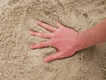 Male Caucasian hand in the salt sand on the beach. Royalty Free Stock Image