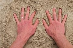 Male Caucasian hand in the salt sand on the beach. Stock Photo