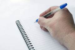 Male Caucasian Hand Writing on a Notepad stock images