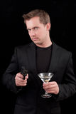 Male caucasian model with a gun. Caucasian male model holding a gun in one hand a martini on the other isolated on a black background Royalty Free Stock Photo