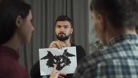 Male Caucasian psychologist listening with interest to patients discussing Rorschach inkblots. Professional