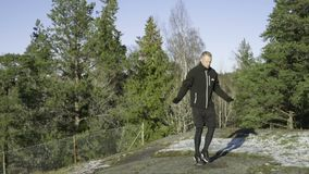 Male caucasian swedish professional boxer jumping rope outdoor in nature. stock video footage