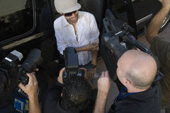 Male Celebrity Being Interviewed. Elevated view of a male celebrity being interviewed by paparazzi royalty free stock photos