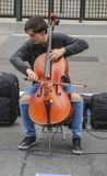 Male cellist performing a classical concert in the street at Paulista Avenue. Sao Paulo, Brazil November 24, 2018: An unidentified male cellist performing a royalty free stock photo