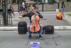 Male cellist performing a classical concert in the street at Paulista Avenue. Sao Paulo, Brazil November 24, 2018: An unidentified male cellist performing a stock photos
