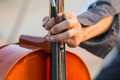 Male cellist`s hand holding cello and bow. Close up of male cellist`s hand holding cello and bow stock images