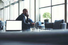 Male CEO is sitting near net-book with copy space screen Royalty Free Stock Images