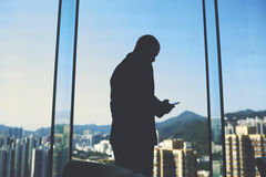 Male CEO is standing in his office near big window with view of business district in China. Silhouette of a man smart financier is calculating inefficient Royalty Free Stock Image