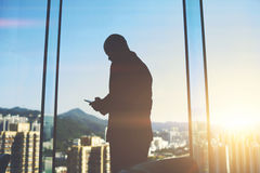 Male CEO is standing in office near big skyscraper window with city view. Silhouette of a man entrepreneur is typing text message on mobile phone to investor to Stock Photo