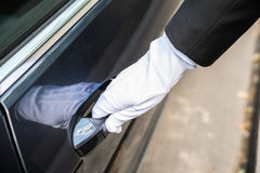 Male Chauffeur Opening Door Of Car. Close-up Of A Male Chauffeur Pulling A Car`s Door Handle Stock Images