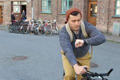 Male checking the time while commuting on his bicycle.  Stock Photo