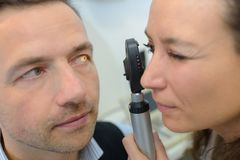 Male checks eyes on modern equipment. Male checks the eyes on the modern equipment Royalty Free Stock Image
